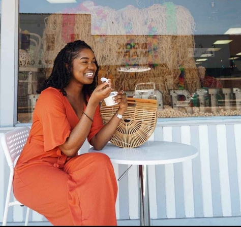 woman smiling and eating outside the pop porium shop